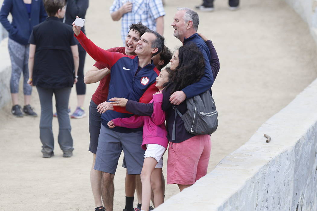 Canadian Prime Minister Justin Trudeau, left, with Los Angeles Mayor Eric Garcetti holding the cell phone, take a selfie with the Duncan family from Los Angeles, as they hike in the Griffith Obser ...