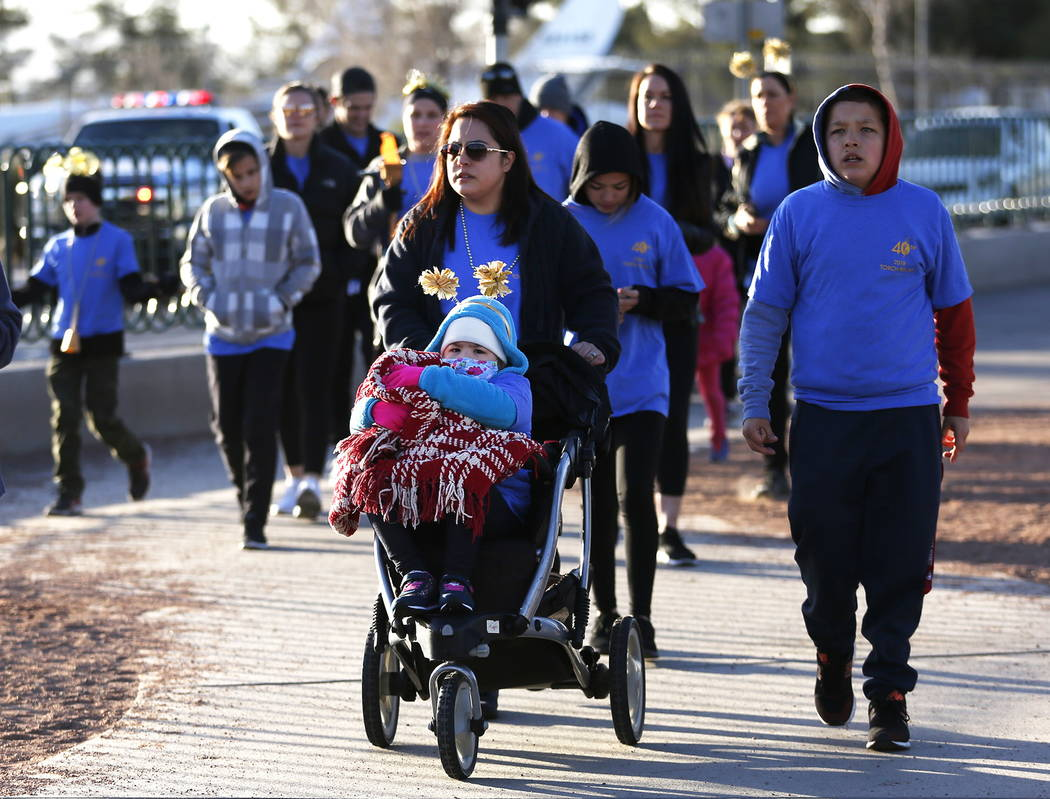 Marci Theriault, 33, of Las Vegas and her 6-year-old daughter, Mia, participate in a torch relay, which was hosted by the Candlelighters Childhood Cancer Foundation of Nevada, in Las Vegas on Sund ...