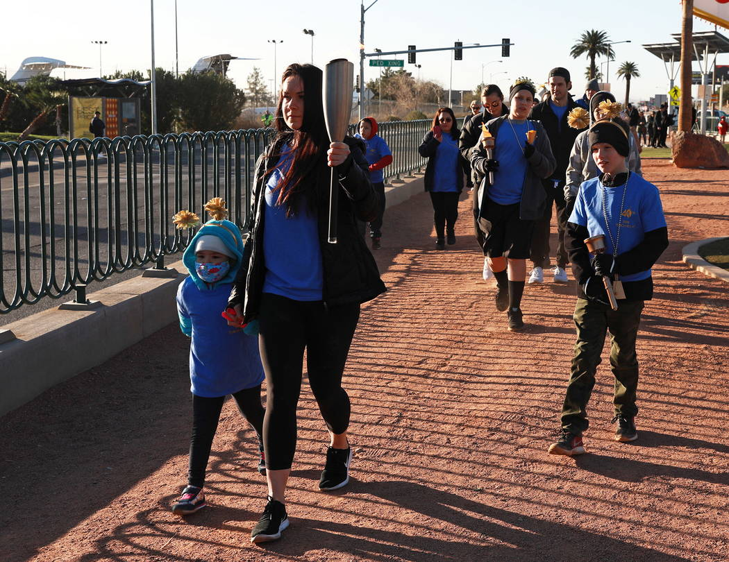 Brittany Herlean, 34, and Mia Theriault, 6, lead the torch relay, which was hosted by the Candlelighters Childhood Cancer Foundation of Nevada, in Las Vegas on Sunday, Feb. 11, 2018. The relay was ...