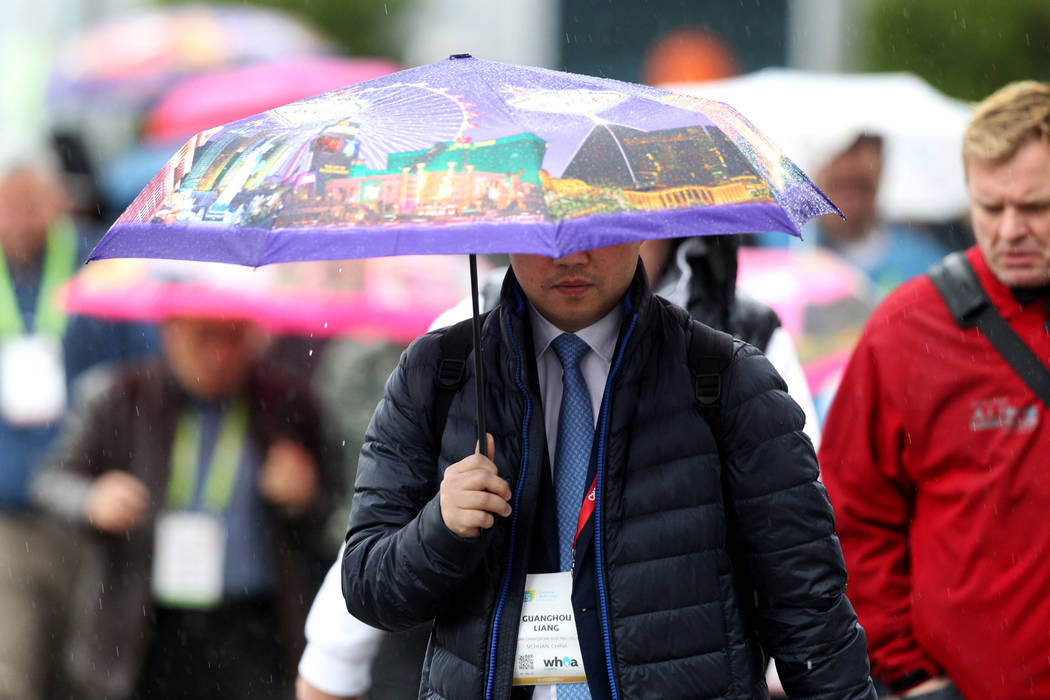 Attendees cross Paradise Road to the Consumer Electronics Show at the Las Vegas Convention Center during a rain storm on Tuesday, Jan. 10, 2018. (K.M. Cannon Las Vegas Review-Journal) @KMCannonPhoto