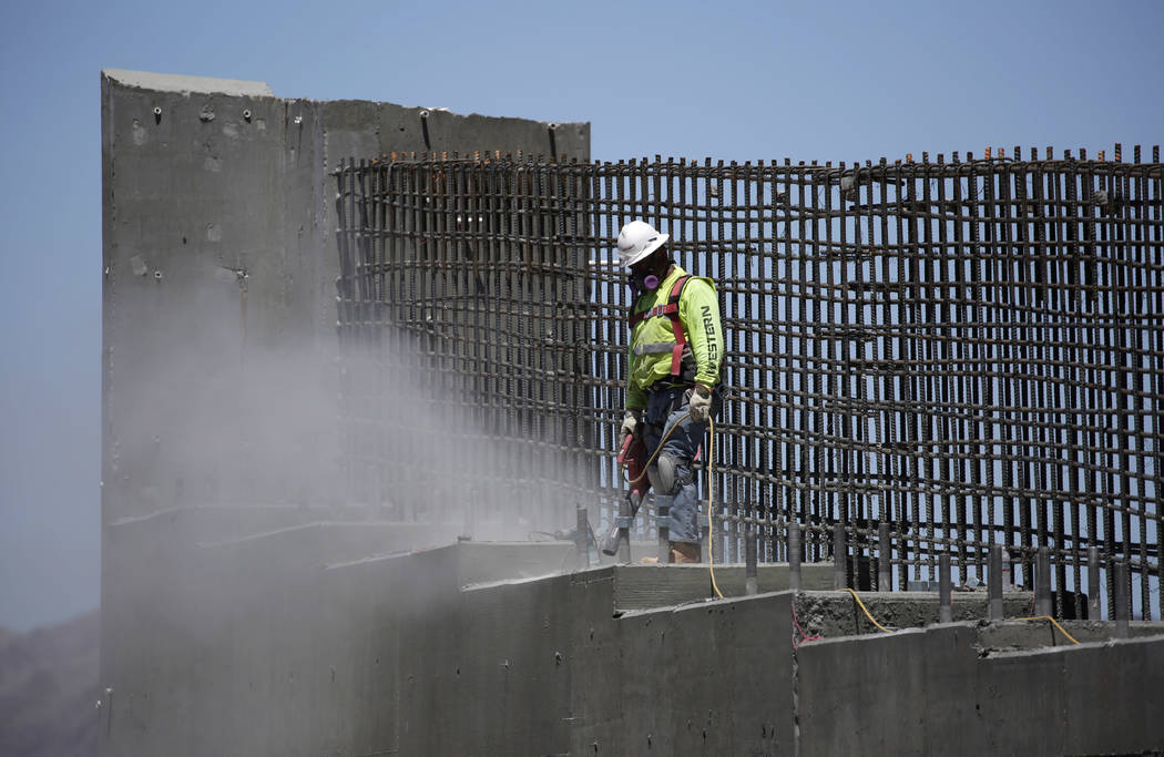 A man works on the Southern Nevada portion of U.S. Interstate 11 near Boulder City, Nev., May 19, 2017. President Donald Trump on Monday, Feb. 12, 2018,  will unveil his long-awaited infrastructur ...