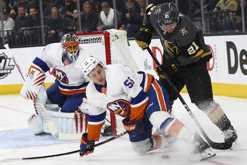 Golden Knights center Cody Eakin (21) tries to move the puck around New York Islanders center Tanner Fritz (56) during an NHL game at T-Mobile Arena in Las Vegas on Thursday, Jan. 25, 2018. Chase  ...