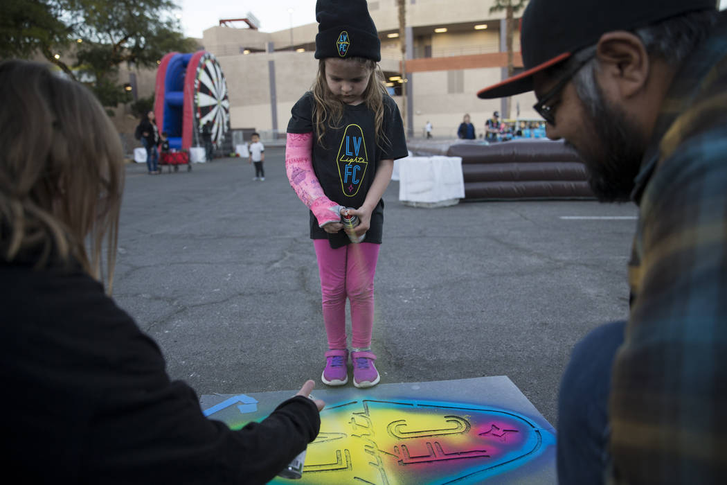 Everleigh Brown, 4, sprays chalk on a stencil of the Las Vegas Lights FC outside of Cashman Field in Las Vegas, Saturday, Feb. 17, 2018. Erik Verduzco Las Vegas Review-Journal @Erik_Verduzco