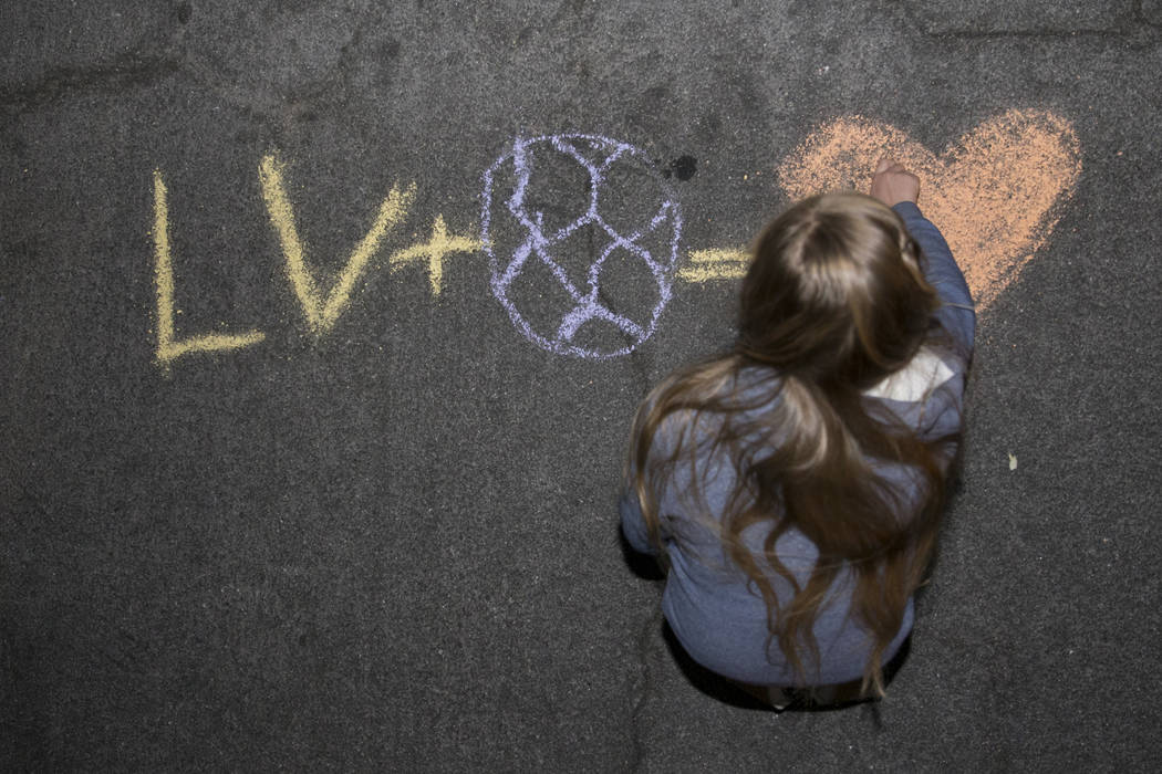 Zoey Jamison, 10, draws on the ground with chalk outside of Cashman Field in Las Vegas before a soccer game between the Las Vegas Lights FC and Vancouver Whitecaps FC, Saturday, Feb. 17, 2018. Eri ...