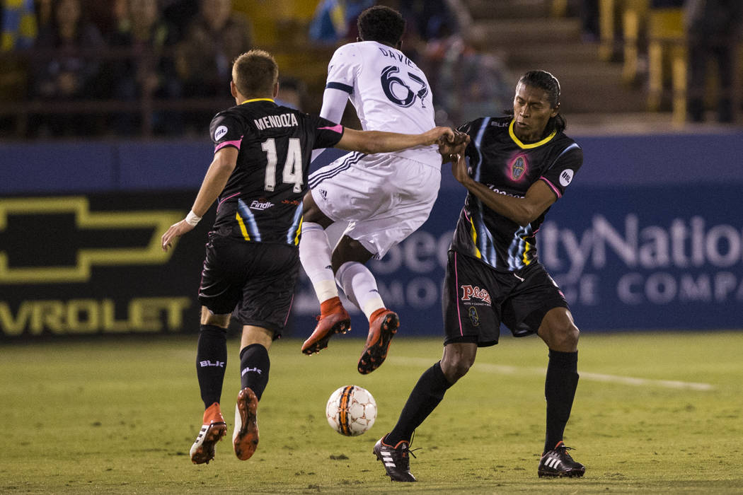 Vancouver Whitecaps FC's Alphonso Davies (67) leaps passed Las Vegas Lights FC's Alex Mendoza (14) and Joel Huiqui (4) in their soccer game at Cashman Field in Las Vegas, Saturday, F ...