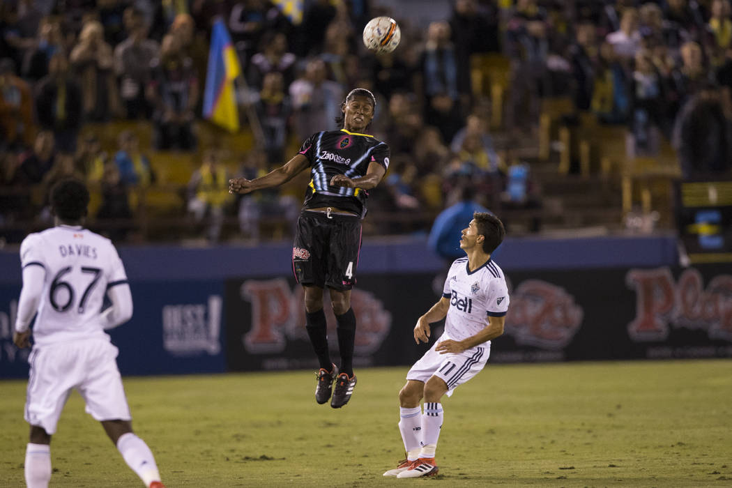 Las Vegas Lights FC's Joel Huiqui (4) connects with the ball as Vancouver Whitecaps FC's Nicola´s Mezquida (11) looks on during their soccer game at Cashman Field in Las Vegas,  ...