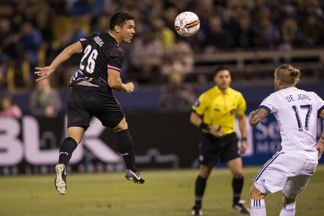 Las Vegas Lights FC's Julian Portugal (26) connects with the ball during a corner kick against Vancouver Whitecaps FC's Marcel de Jong (17) in the soccer game at Cashman Field in Las ...