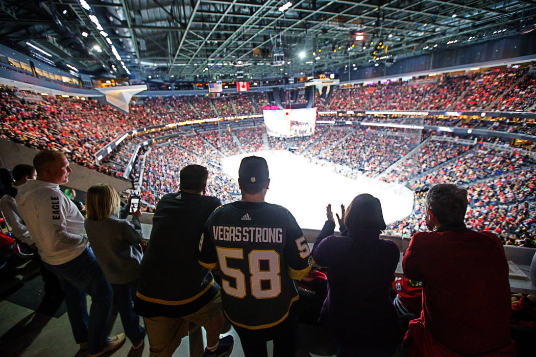 Hockey fans, including Zack Mueller in the Vegas Strong jersey, center, with his friend Will Seiber, left, take in the action from the standing room only area as the Golden Knights play the Chicag ...