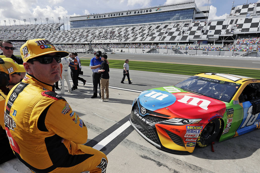 Kyle Busch, left, watches the leaderboard during qualifying for the NASCAR Daytona 500 auto race at Daytona International Speedway, Sunday, Feb. 11, 2018, in Daytona Beach, Fla. (AP Photo/John Raoux)