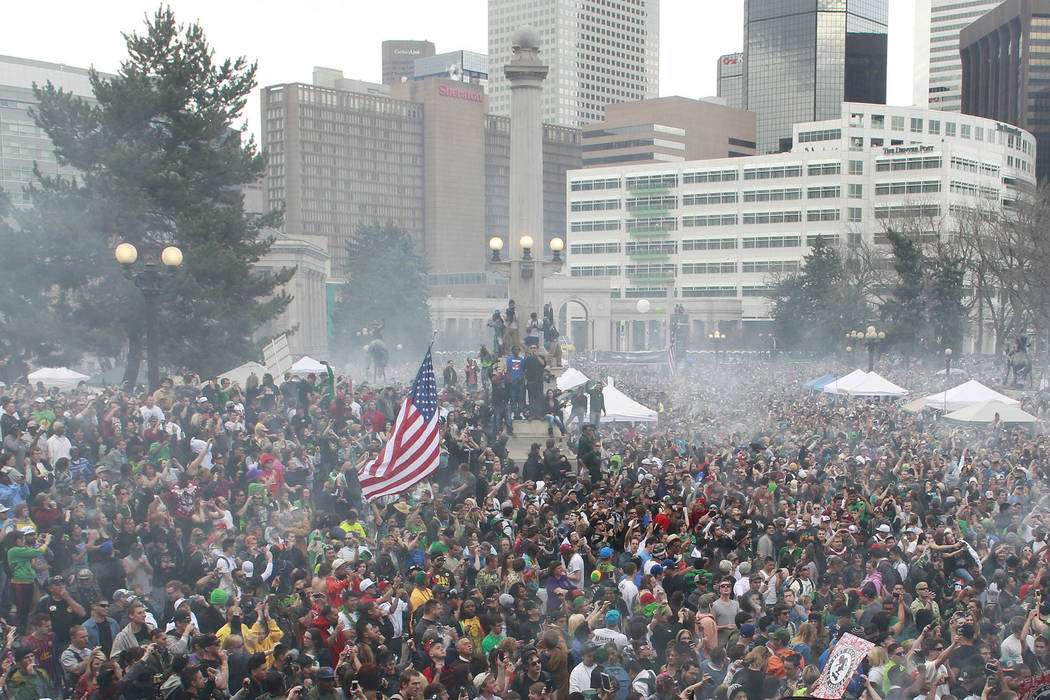 Members of a crowd numbering tens of thousands smoke marijuana at the Denver 4/20 pro-marijuana rally at Civic Center Park in Denver, April 20, 2013. According to a report released on Monday, Feb. ...