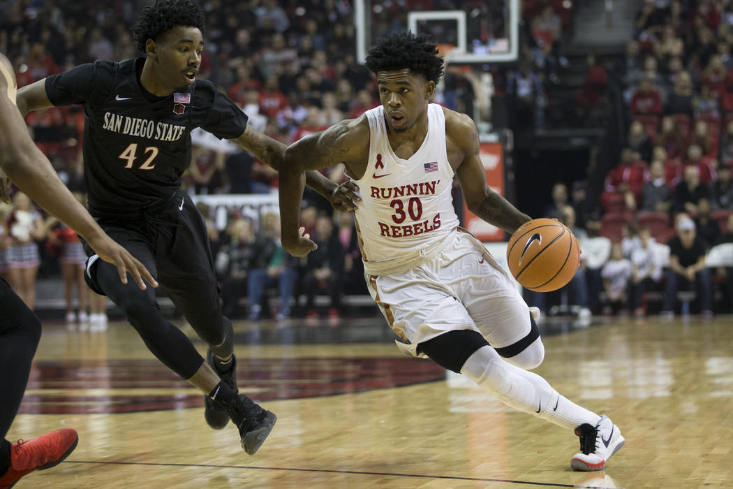 UNLV Rebels guard Jovan Mooring (30) drives the ball against pressure from San Diego State Aztecs guard Jeremy Hemsley (42) at the Thomas & Mack Center in Las Vegas, Saturday, Jan. 27, 2018. E ...