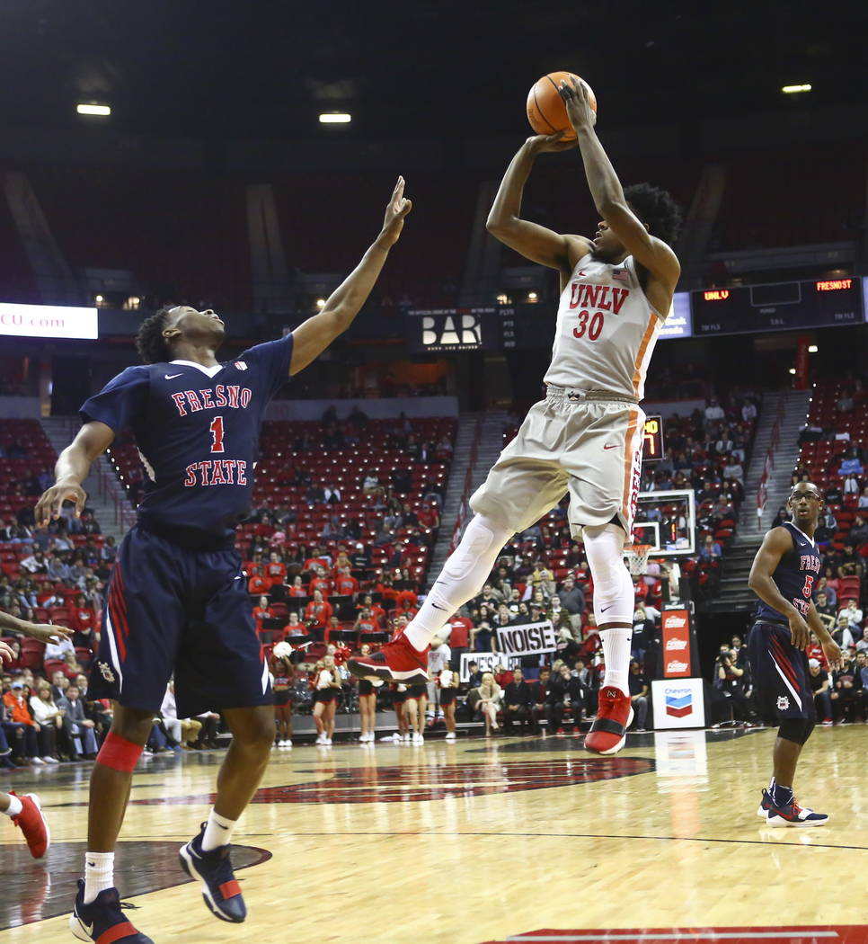 UNLV Rebels guard Jovan Mooring (30) goes up to shoot over Fresno State Bulldogs guard Jaron Hopkins (1) during the first half of a basketball game at the Thomas & Mack Center in Las Vegas on  ...