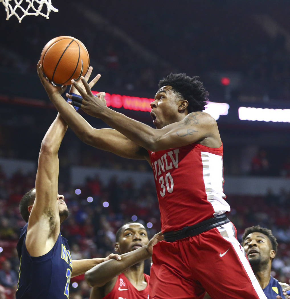 UNLV guard Jovan Mooring (30) goes to the basket over UNR guard Kendall Stephens (21) during the first half of a basketball game at the Thomas & Mack Center in Las Vegas on Wednesday, Feb. 28, ...