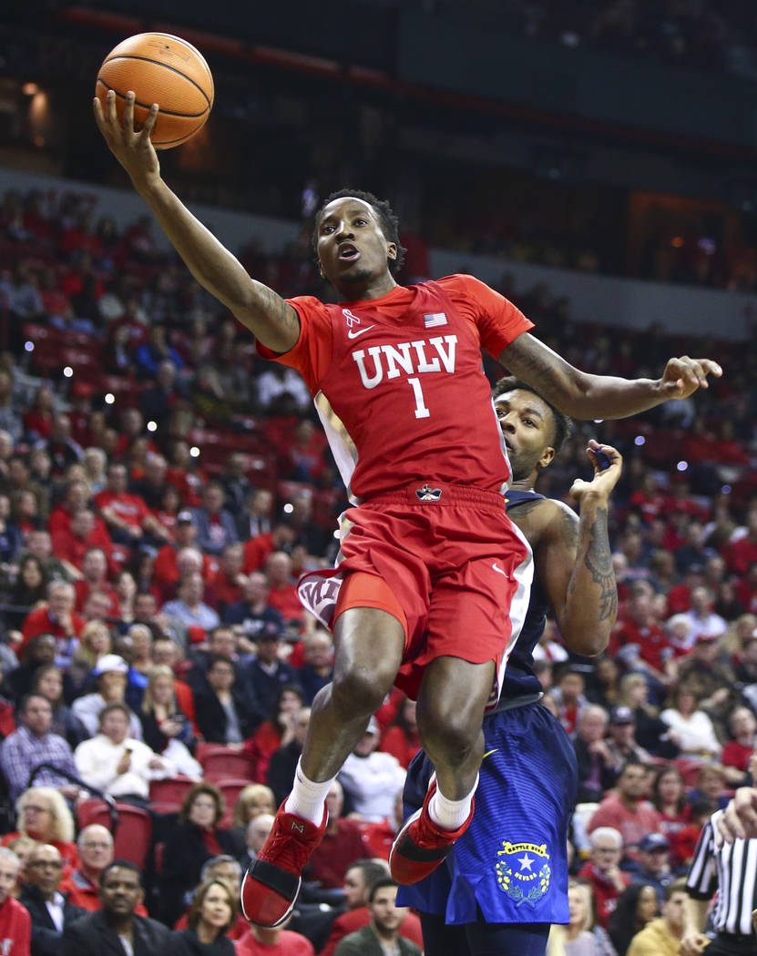 UNLV guard Kris Clyburn (1) goes to the basket past UNR guard Jordan Caroline (24) during the first half of a basketball game at the Thomas & Mack Center in Las Vegas on Wednesday, Feb. 28, 20 ...
