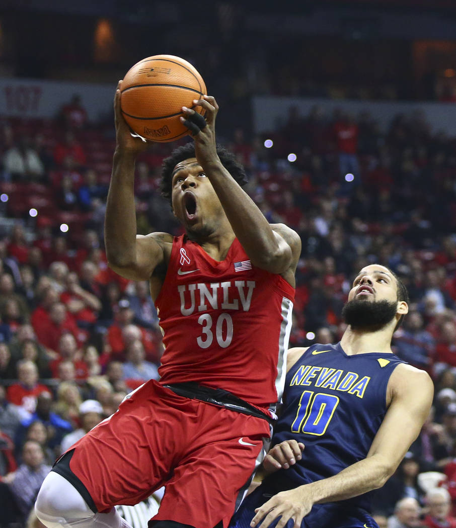 UNLV guard Jovan Mooring (30) goes to the basket over UNR forward Caleb Martin (10) during the first half of a basketball game at the Thomas & Mack Center in Las Vegas on Wednesday, Feb. 28, 2 ...