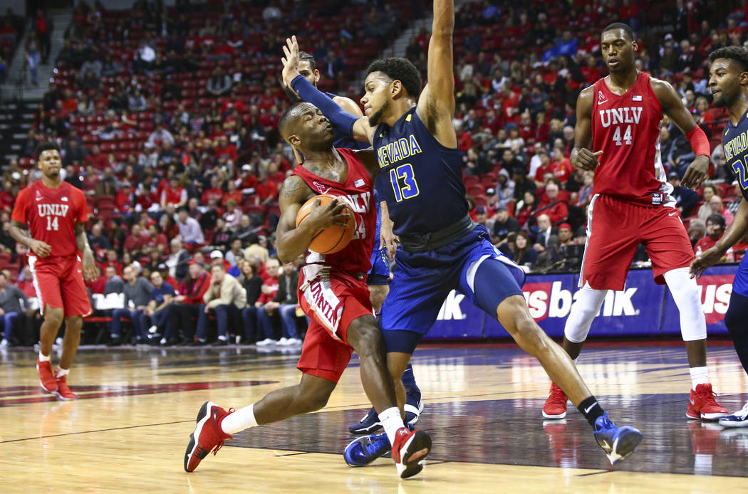 UNLV guard Jordan Johnson (24) drives against UNR guard Hallice Cooke (13) during the second half of a basketball game at the Thomas & Mack Center in Las Vegas on Wednesday, Feb. 28, 2018. UNR ...