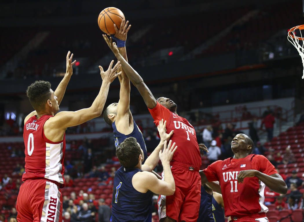 UNLV guards Kris Clyburn (1) and Jay Green (0) try to get a rebound over UNR guard Kendall Stephens (21) during the second half of a basketball game at the Thomas & Mack Center in Las Vegas on ...