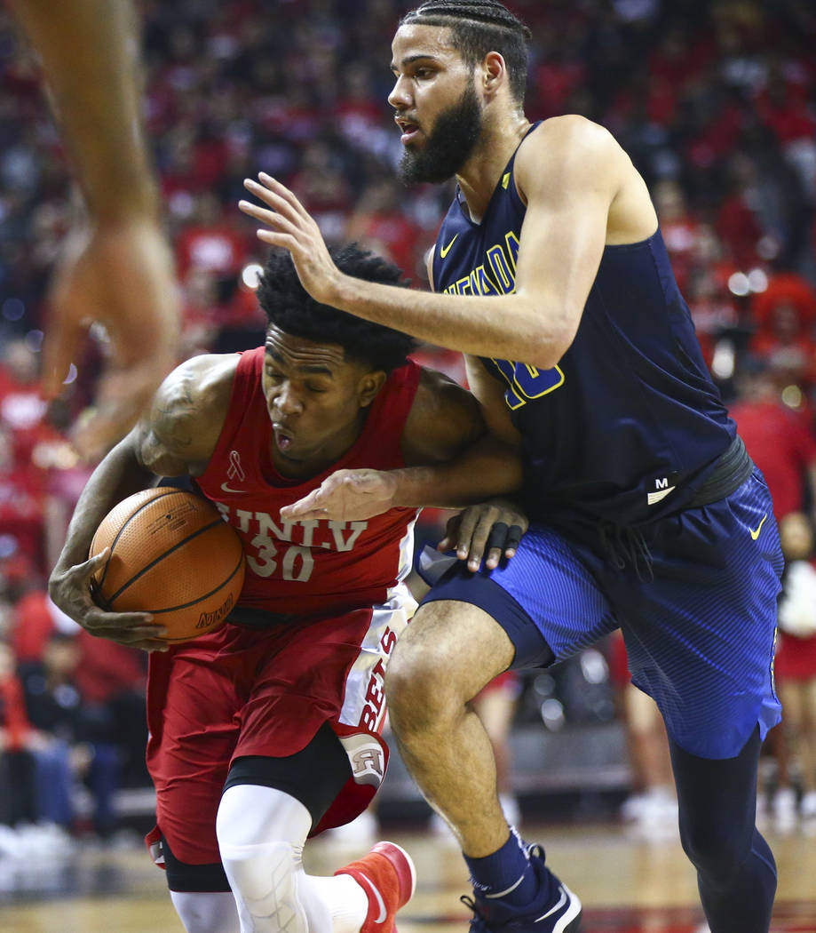 UNLV guard Jovan Mooring (30) drives against UNR forward Caleb Martin (10) during the first half of a basketball game at the Thomas & Mack Center in Las Vegas on Wednesday, Feb. 28, 2018. Chas ...