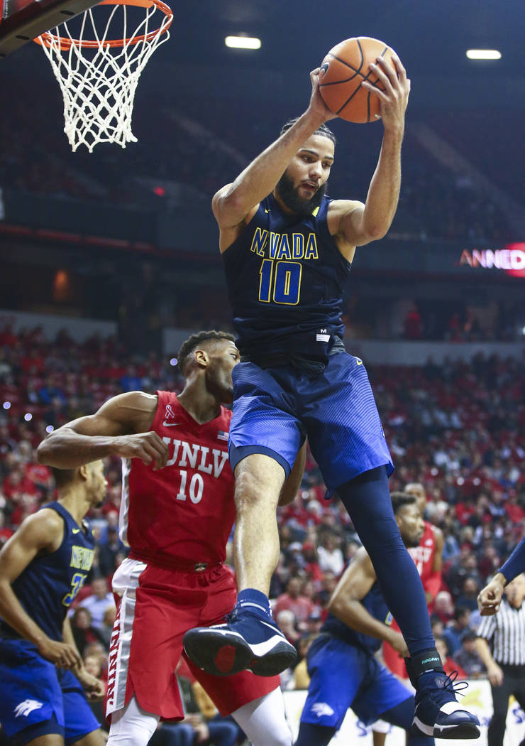 UNR forward Caleb Martin (10) gets a rebound over UNLV forward Shakur Juiston (10) during the first half of a basketball game at the Thomas & Mack Center in Las Vegas on Wednesday, Feb. 28, 20 ...