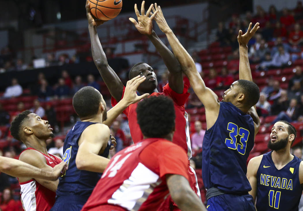 UNR guard Josh Hall (33) defends as UNLV forward Cheikh Mbacke Diong (34) looks for an open shot during the second half of a basketball game at the Thomas & Mack Center in Las Vegas on Wednesd ...