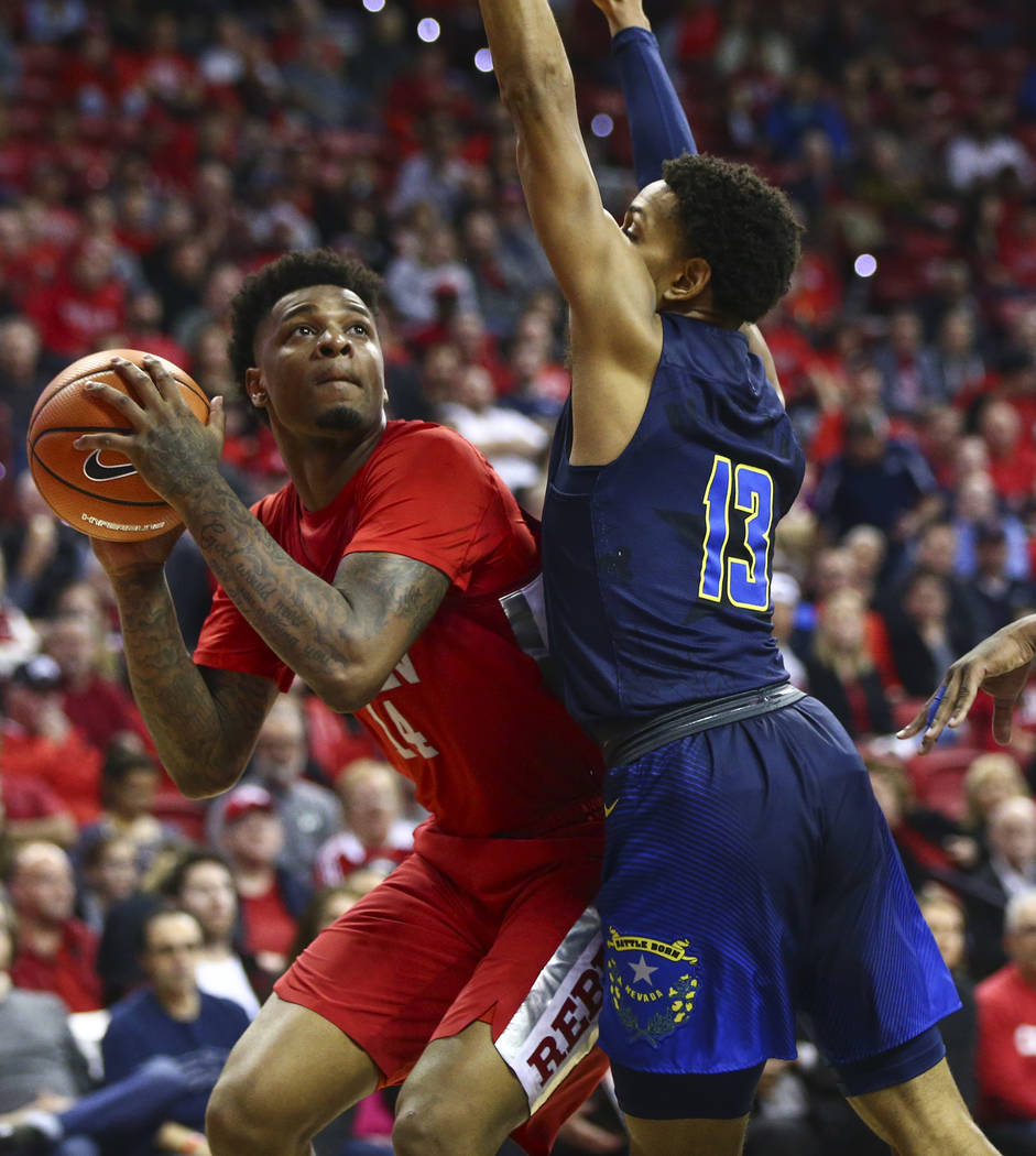 UNLV forward Tervell Beck (14) looks to shoot against UNR guard Hallice Cooke (13) during the first half of a basketball game at the Thomas & Mack Center in Las Vegas on Wednesday, Feb. 28, 20 ...