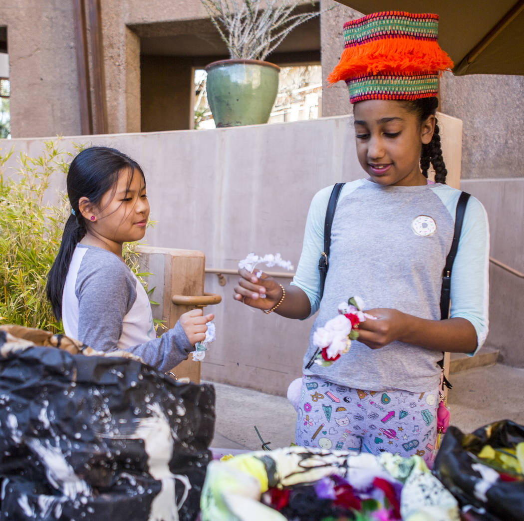 Laila Williams, 9, right, of Las Vegas works on making a rose headdress while Kayla Lee, 10, of Las Vegas watches during a celebration of Black History Month at the Springs Preserve on Saturday, F ...