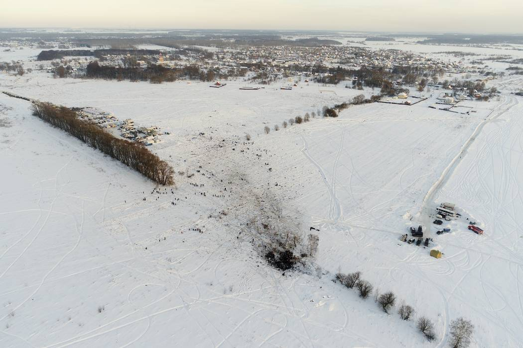 Emergency workers explore the site of a AN-148 plane crash in Stepanovskoye village, about 25 miles from the Domodedovo airport, Russia, Monday, Feb. 12, 2018. Emergency teams combed the snowy fie ...