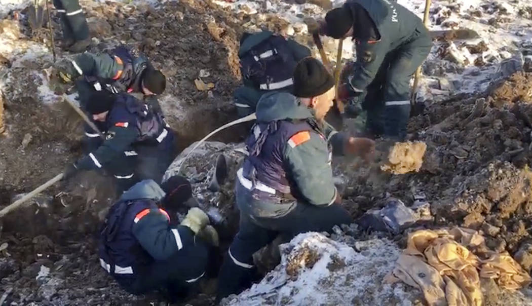 Emergency personnel work at the scene of an AN-148 plane crash in Stepanovskoye village, about 25 miles from the Domodedovo airport, Russia, Tuesday, Feb. 13, 2018. Emergency teams combed the snow ...