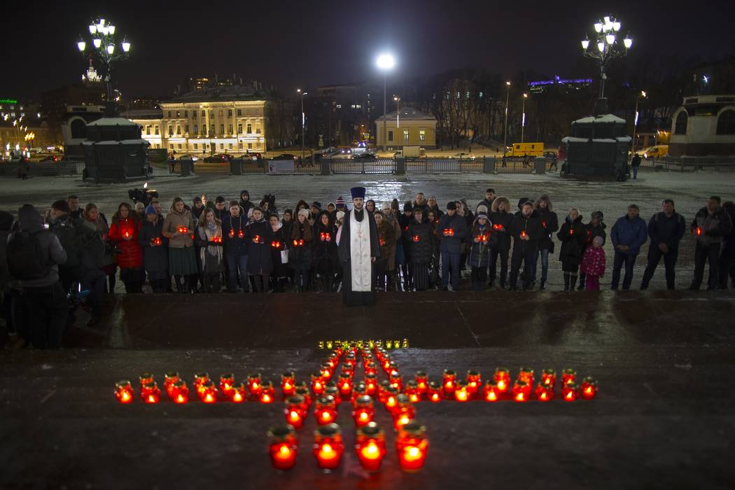 Orthodox youth with a priest gather at the Cathedral of Christ the Savior in Moscow lighting 71 candles in memory of those killed in the An-148 plane crash, Monday, Feb. 12, 2018.(Alexander Zemlia ...