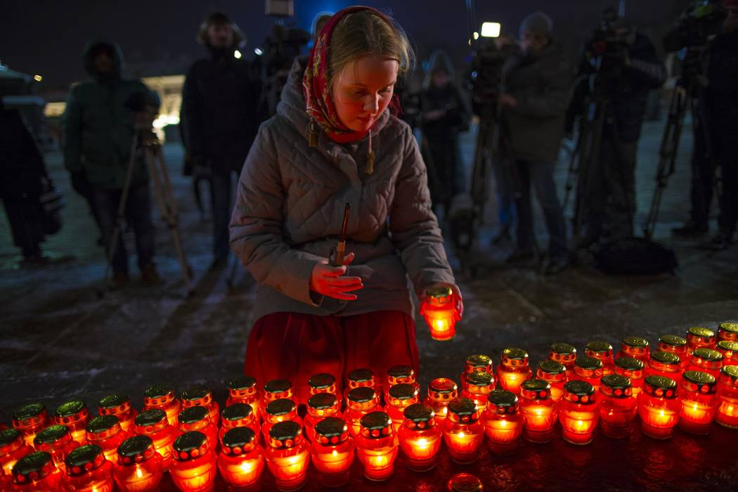 A girl places a candle as a group gather at the Cathedral of Christ the Savior in Moscow to light 71 candles in memory of those killed in the An-148 plane crash on Monday, Feb. 12, 2018. (Alexande ...