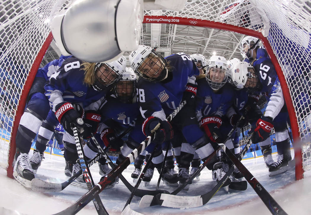 Players from the United States pose for the camera as they gather around the goal before the preliminary round of the women's hockey game against the team from Russia at the 2018 Winter Olympics i ...