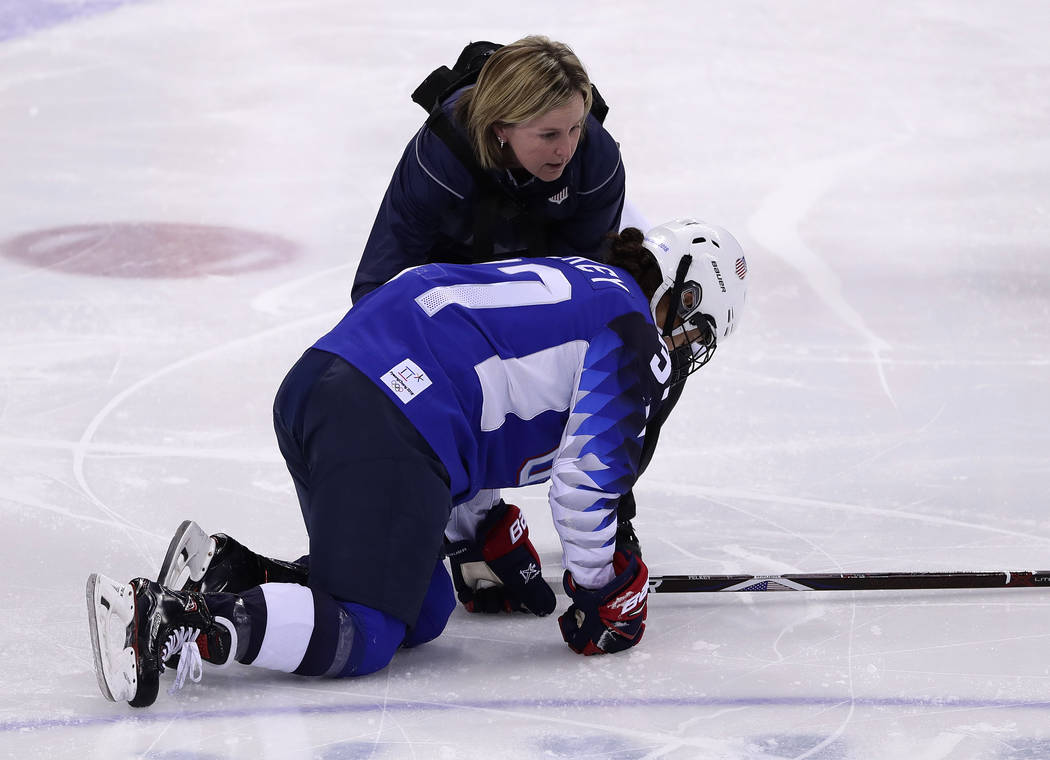 Amanda Pelkey, of the United States, is checked by team doctor Ally Howe during the first period of the preliminary round of the women's hockey game against the team from Russia at the 2018 Winter ...