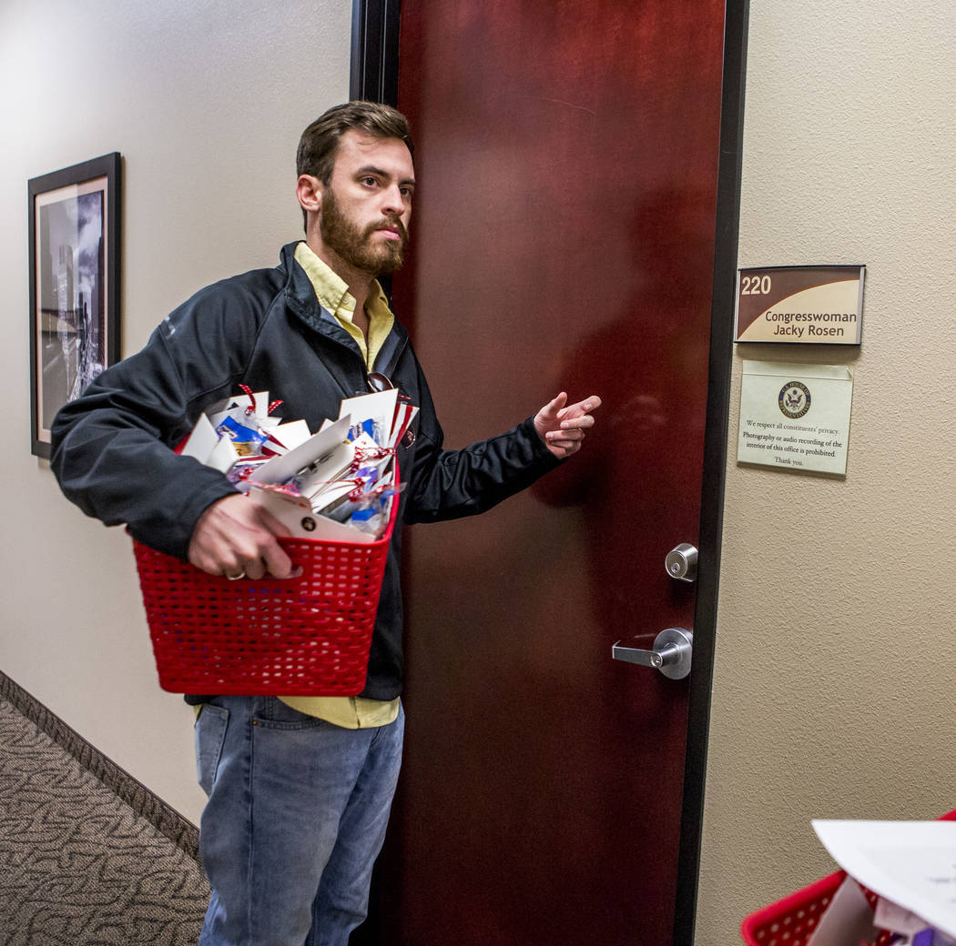 Will Sexauer, deputy state director with the Republican Party of Nevada, knocks on the door to deliver crumb cakes to Nevada Democratic Rep. Jacky Rosen's office near Green Valley on Wednesday, Fe ...