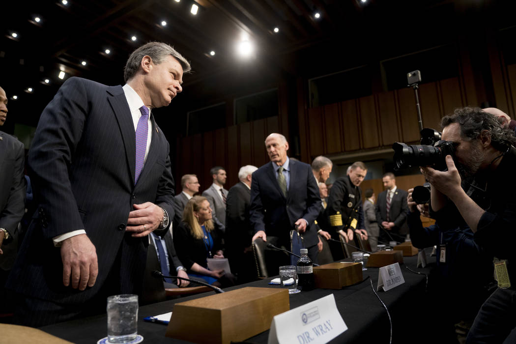 FBI Director Christopher Wray, left, and Director of National Intelligence Dan Coats, center, arrive for a Senate Select Committee on Intelligence hearing on worldwide threats, Tuesday, Feb. 13, 2 ...