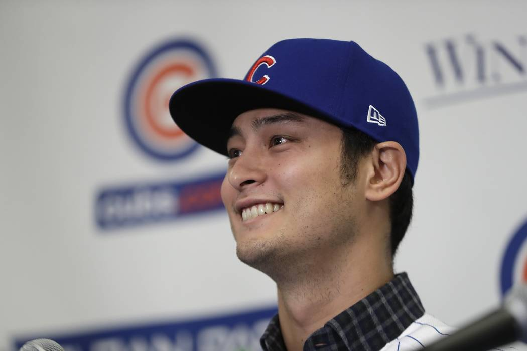 Chicago Cubs starting pitcher Yu Darvish responds during a media availability at the team's spring training baseball facility Tuesday, Feb. 13, 2018, in Mesa, Ariz. Darvish signed a $126 million,  ...