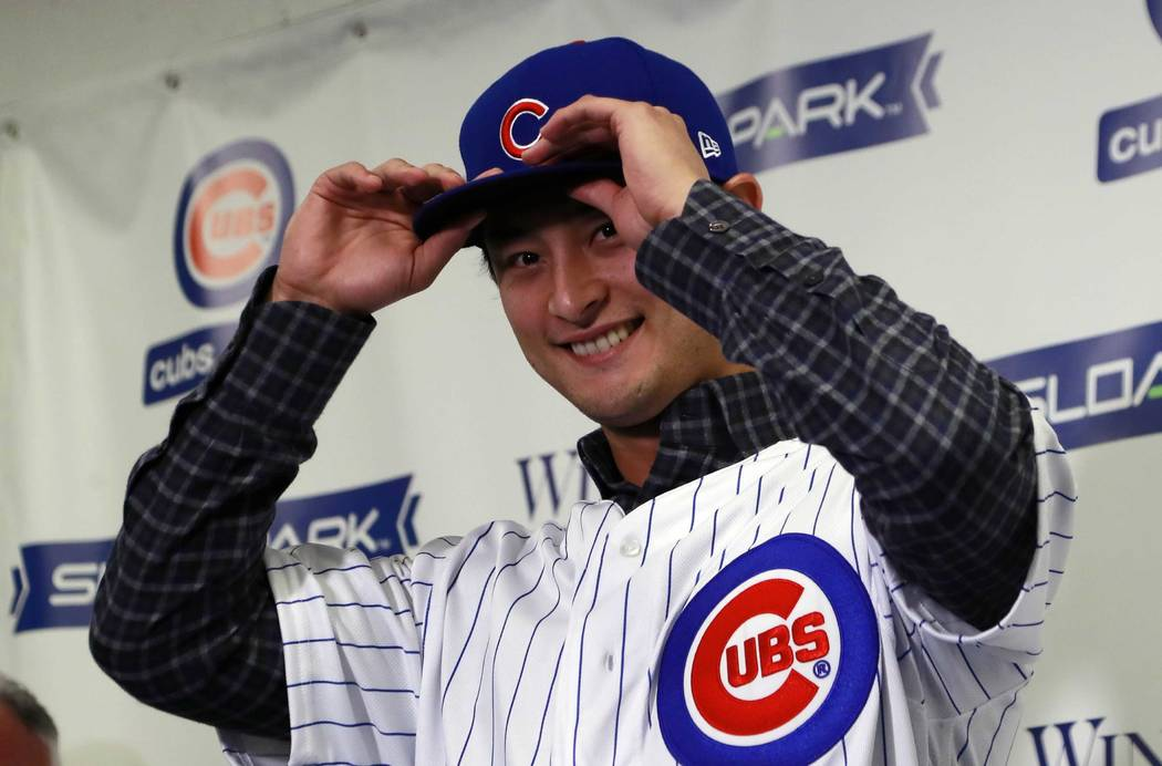 Chicago Cubs starting pitcher Yu Darvish tries on the team's cap during a media availability at the team's spring training baseball facility Tuesday, Feb. 13, 2018, in Mesa, Ariz. Darvish signed a ...