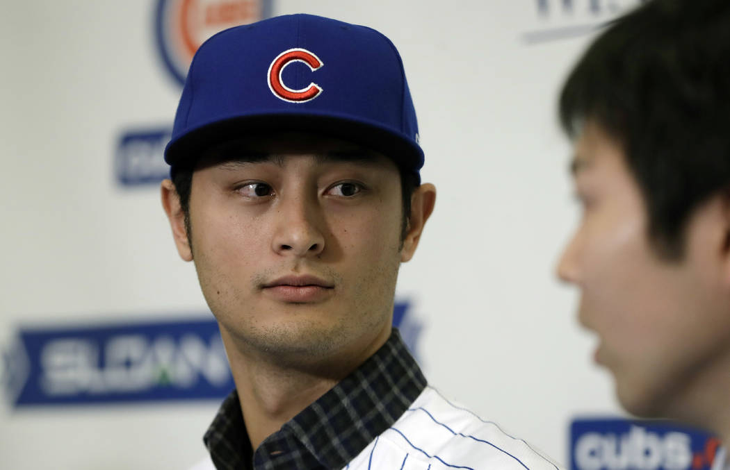 Chicago Cubs starting pitcher Yu Darvish looks towards interpreter Daichi Sekizaki during a media availability at the team's spring training baseball facility Tuesday, Feb. 13, 2018, in Mesa, Ariz ...