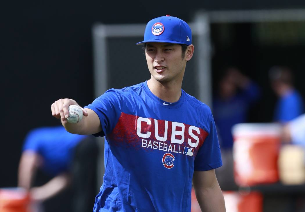 Chicago Cubs starting pitcher Yu Darvish takes a break from warmup pitches at the team's spring training baseball facility Tuesday, Feb. 13, 2018, in Mesa, Ariz. Darvish signed a $126 million, six ...