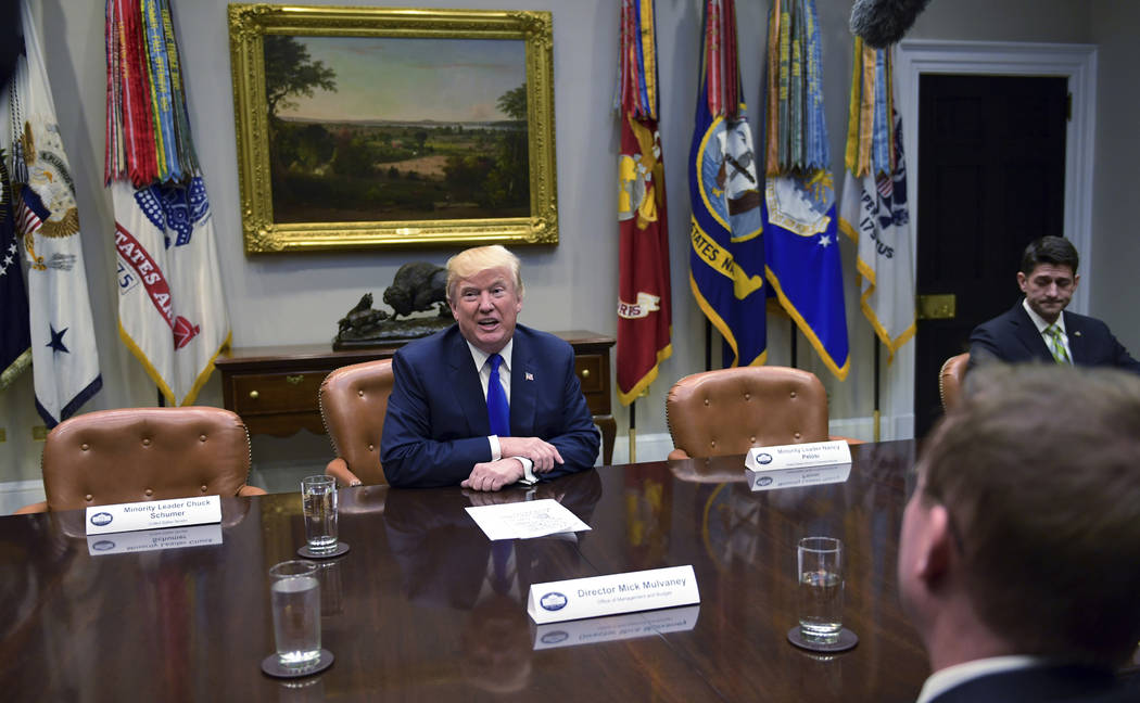 President Donald Trump, center speaks in the Roosevelt Room of the White House in Washington, Tuesday, Nov. 28, 2017, during a meeting with Republican congressional leaders. House Speaker Paul Rya ...