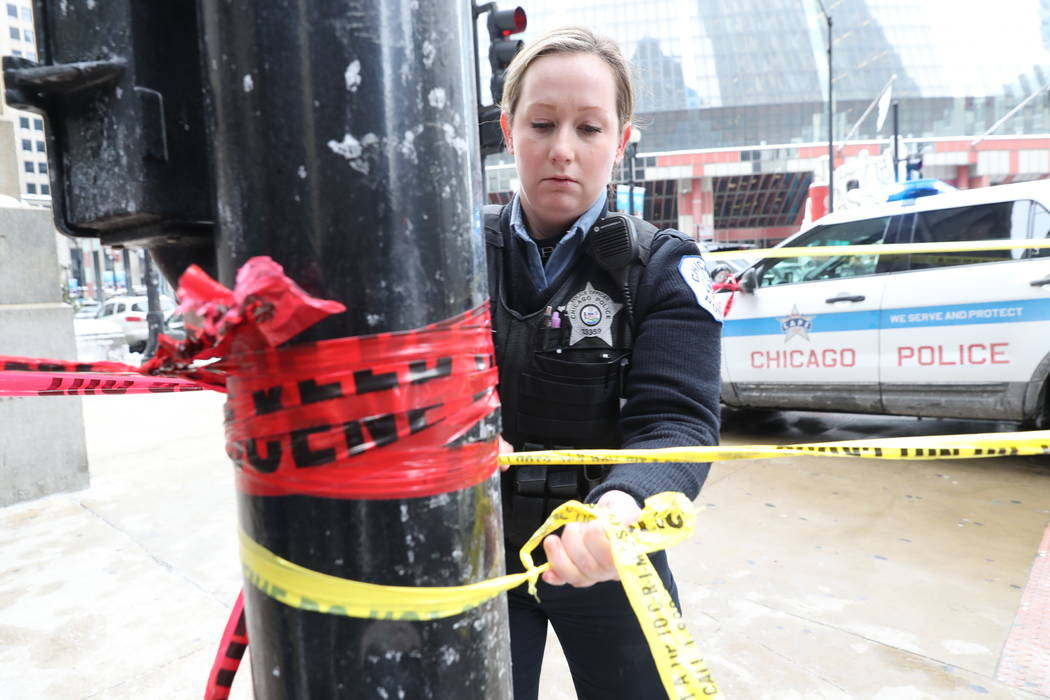 A Chicago police officer strings crime scene tape across from the Thompson Center after an off-duty officer was shot  in Chicago, Tuesday, Feb. 13, 2018. (John J. Kim/Chicago Tribune via AP)