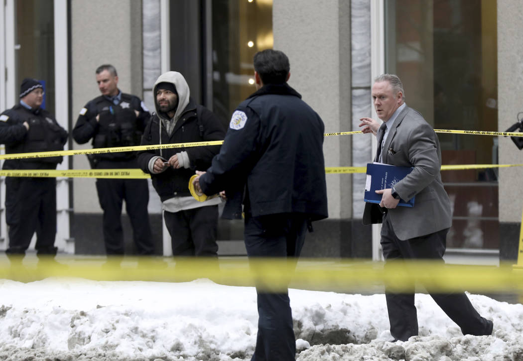 Pedestrians navigate crime scene tape as police guard the scene where an off-duty officer was shot while assisting a tactical team at a state government office building, Tuesday, Feb. 13, 2018, in ...
