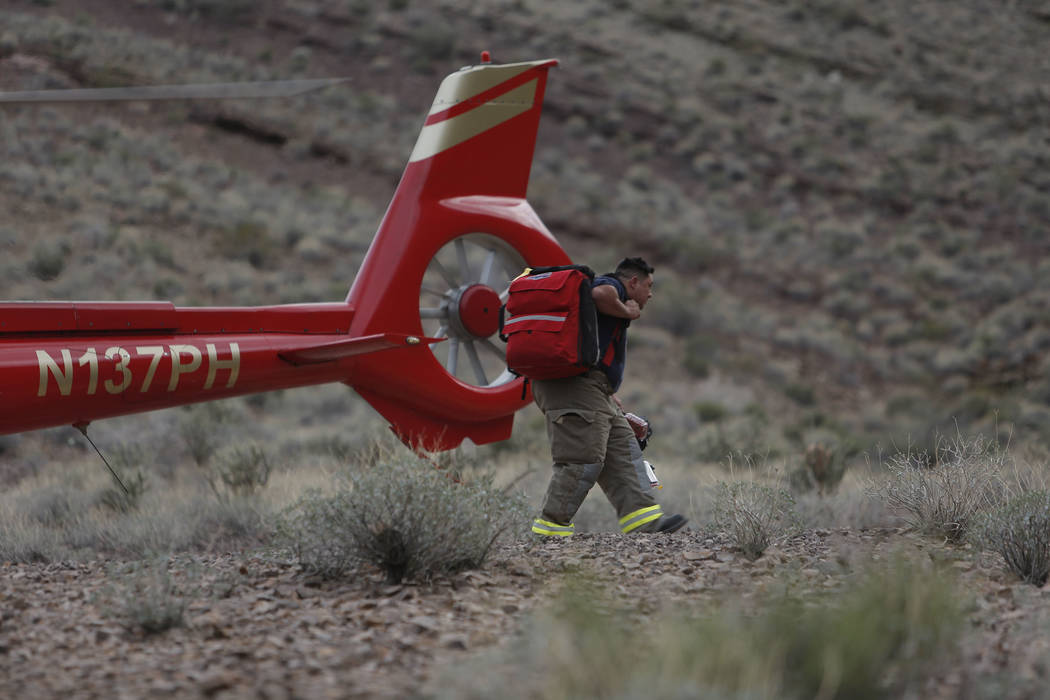 Emergency personnel go to the scene of a deadly tour helicopter crash in the Grand Canyon, Arizona, Saturday, Feb. 10, 2018. The crash killed three people and injured four others.  Photo by Teddy  ...