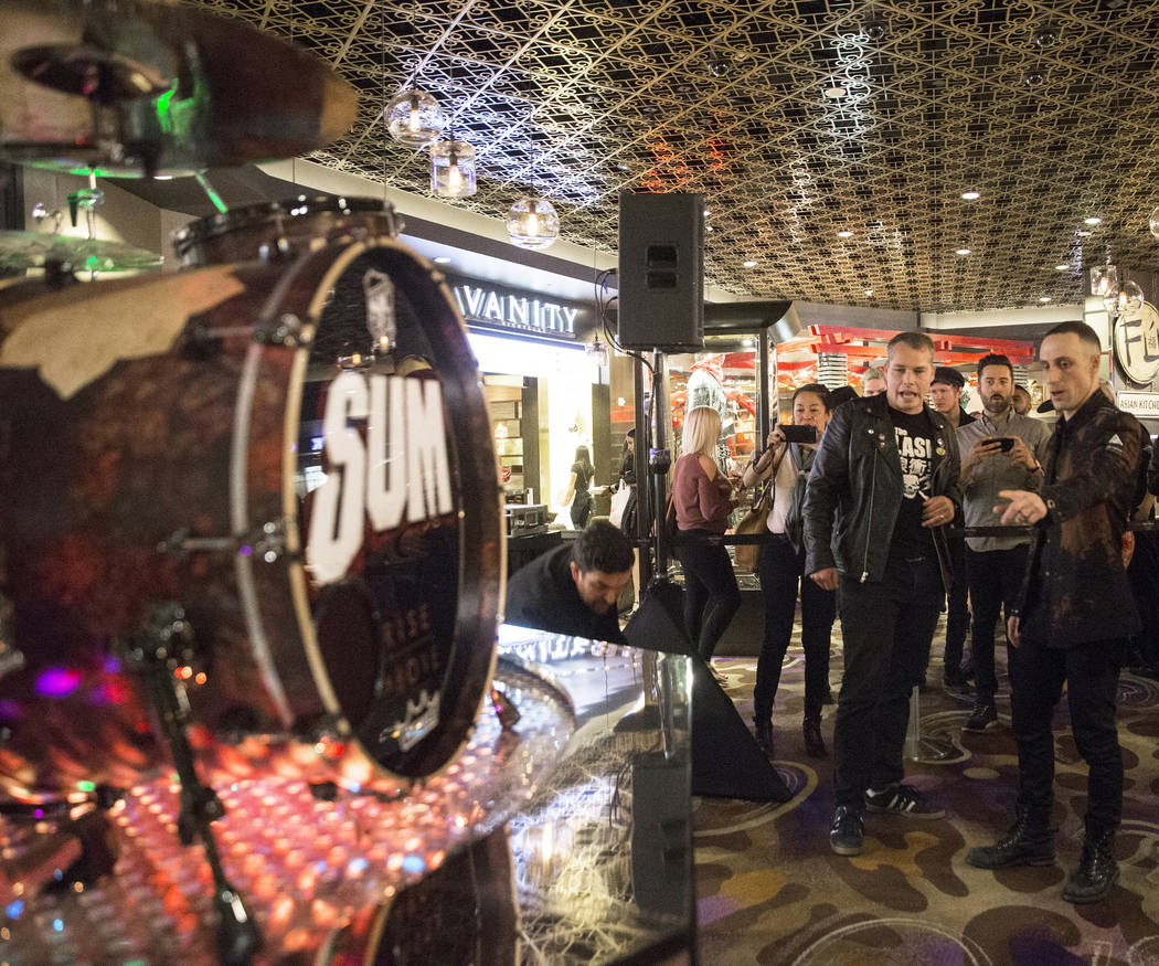 Artist Shepard Fairey, middle, and Sum 41 drummer Frank Zummo point out features of a custom a drumkit/art project called Rise Above on Friday, February 16, 2018, at The Hard Rock hotel-casino, in ...