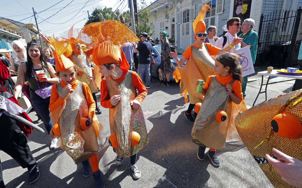 Children dressed as goldfish walk in the Society de Sainte Anne parade, on Mardi Gras day in New Orleans, Tuesday, Feb. 13, 2018. (AP Photo/Gerald Herbert)