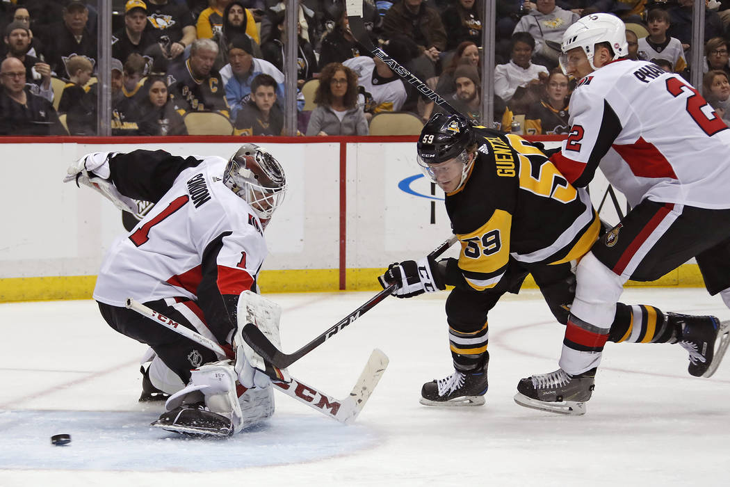 Pittsburgh Penguins' Jake Guentzel (59) gets a shot past Ottawa Senators goaltender Mike Condon (1) for a goal with Dion Phaneuf (2) defending during the second period of an NHL hockey game in Pit ...