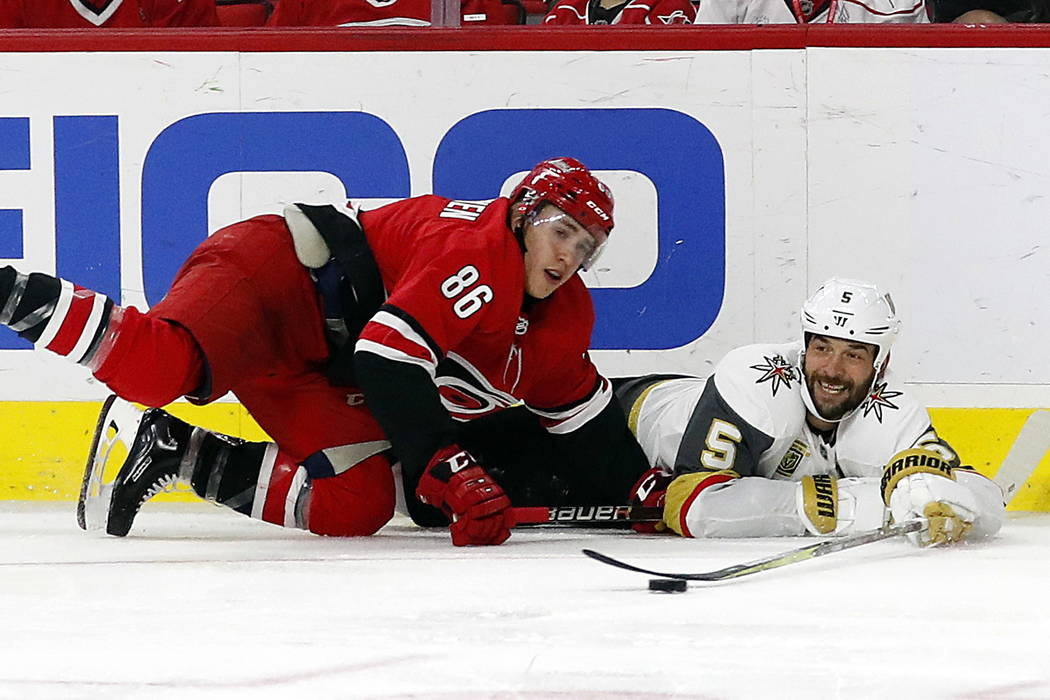 Vegas Golden Knights' Deryk Engelland (5) tries to pass the puck after colliding with Carolina Hurricanes' Teuvo Teravainen (86) during the second period of an NHL hockey game, Sunday, Jan. 21, 20 ...