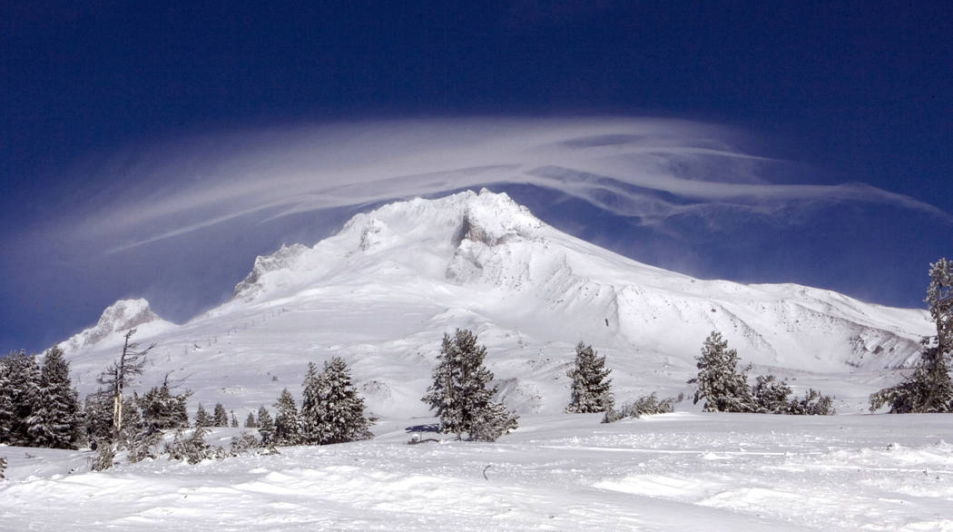 In this Dec. 13, 2009, file photo, a cloud forms over Mount Hood as seen from Government Camp, Ore. Authorities say a rescue effort is underway, Tuesday, Feb. 13, 2018, for a climber who fell on M ...
