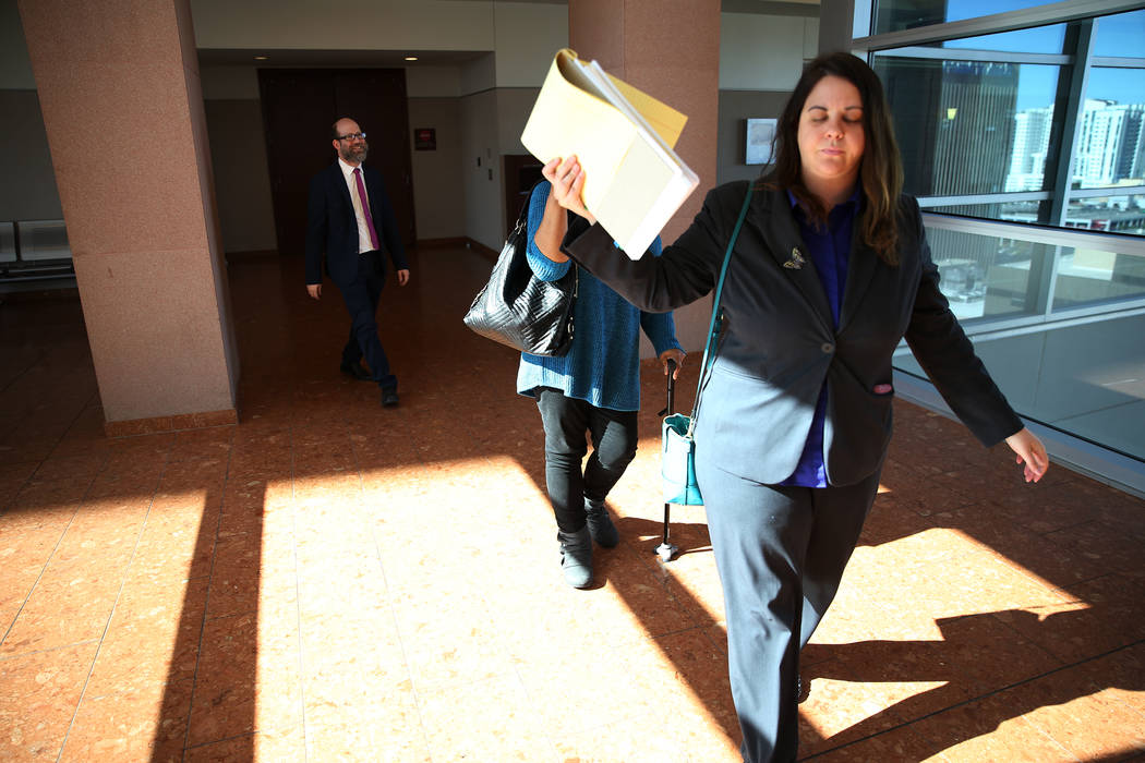 Janet Solander, center, accused of abusing her adopted children, with attorneys Caitlyn McAmis, right, and Dayvid Figler, leaves court for a lunch break during opening statements in her trial at t ...