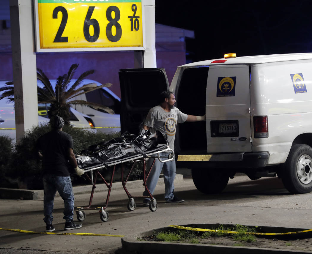 Police move a body into a coroner van at the scene of a Mardi Gras day shooting that left at least one dead and others injured, in the lower ninth ward in New Orleans, Tuesday, Feb. 13, 2018. (AP  ...