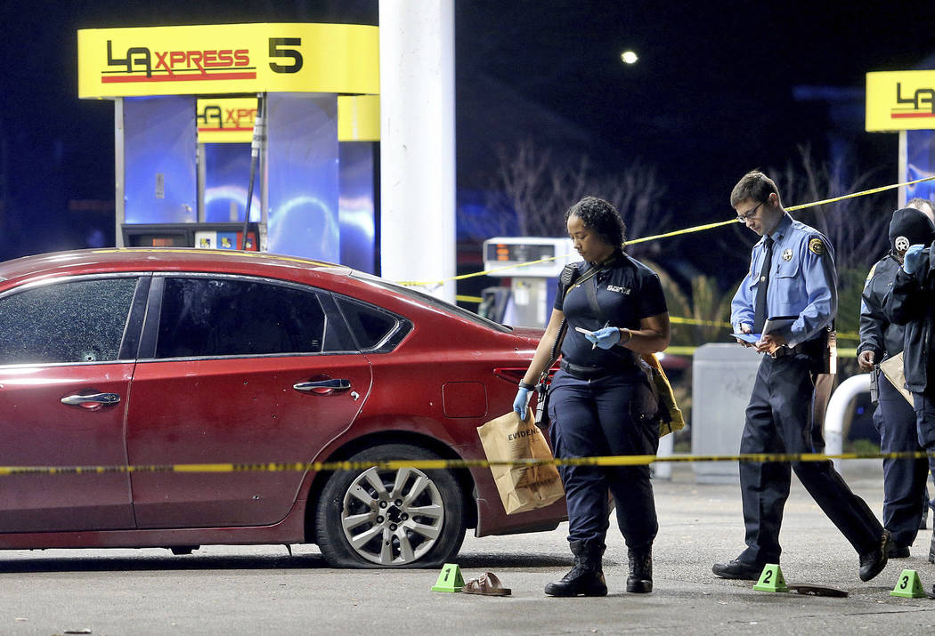 Crime scene technicians gather evidence next to a bullet-riddled red Nissan sedan with a homicide victim inside as New Orleans Police investigate after several people were shot, in the lower Ninth ...